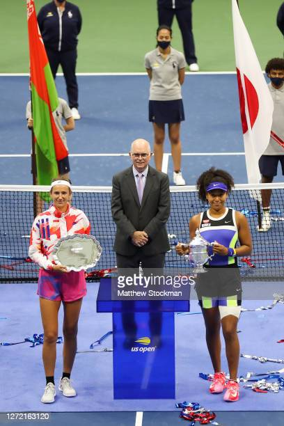 Naomi Osaka of Japan holds the championship trophy and Victoria Azarenka of Belarus holds the finalist trophy after being awarded them by USTA...