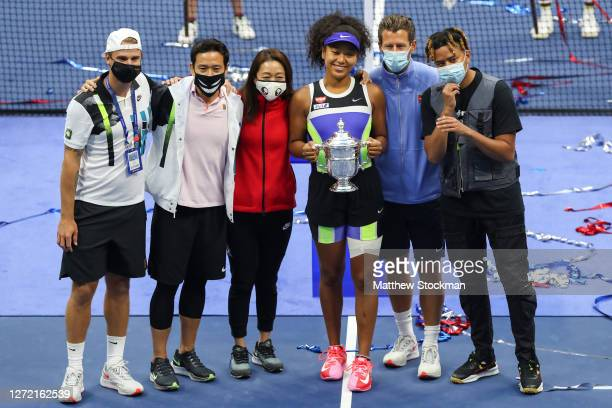 Naomi Osaka of Japan holds the trophy and celebrates with her team and boyfriend, rapper YBN Cordae , after winning her Women's Singles final match...