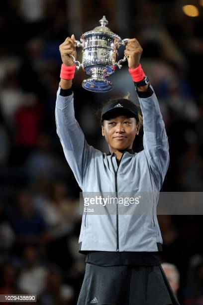 Naomi Osaka of Japan holds up the trophy after winning the Women's Singles finals match against Serena Williams of the United States on Day Thirteen...