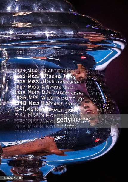Naomi Osaka of Japan is reflected as she holds the Daphne Akhurst Memorial Cup following victory in her Women's Singles Final match against Petra...