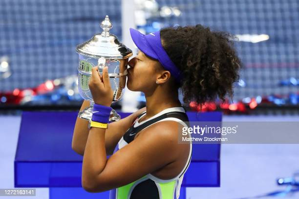 Naomi Osaka of Japan kisses the trophy in celebration after winning her Women's Singles final match against Victoria Azarenka of Belarus on Day...