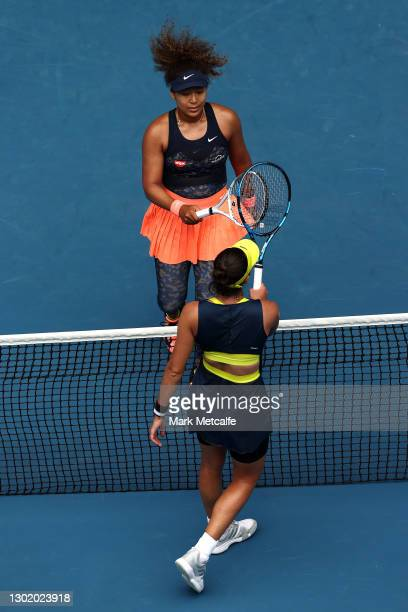 Naomi Osaka of Japan knocks racquet at the net with Garbine Muguruza of Spain following victory in their Women's Singles fourth round match during...