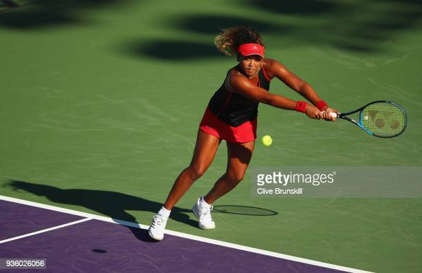 Naomi Osaka of Japan plays a backhand against Serena Williams of the United States in their first round match during the Miami Open Presented by Itau...