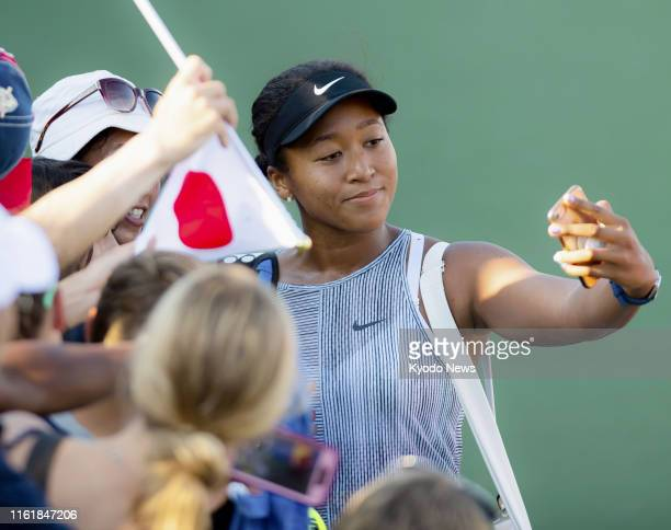 Naomi Osaka of Japan poses for a photo with fans after beating Hsieh Suwei of Taiwan in the third round of the Western amp Southern Open in...