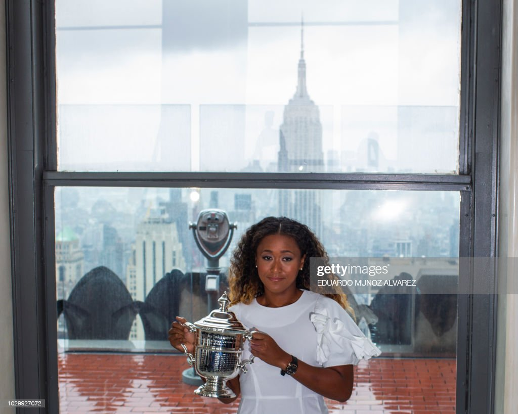 Naomi Osaka of Japan poses with her championship trophy at the Rock Observation Deck at Rockefeller Center in New York on September 09, 2018, the morning after defeating Serena Williams of the United States, winning the 2018 US Open Women's Singles Finals.