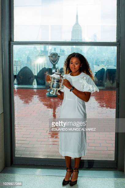 Naomi Osaka of Japan poses with her championship trophy at the Rock Observation Deck at Rockefeller Center in New York on September 09 the morning...