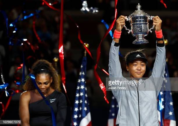 Naomi Osaka of Japan poses with the championship trophy after winning the Women's Singles finals match against Serena Williams of the United States...