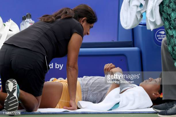 Naomi Osaka of Japan receives medical attention from WTA trainer Reshma Rathod in the third set of her match against Sofia Kenin during the Western...