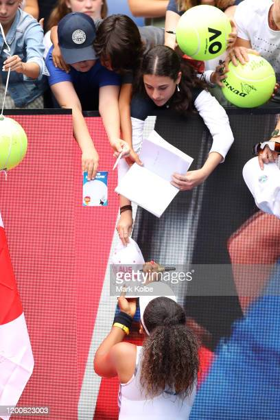 Naomi Osaka of Japan signs autographs for fans after winning her Women's Singles first round match against Marie Bouzkova of Czech Republic on day...