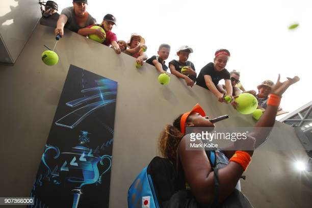 Naomi Osaka of Japan signs autographs for fans after winning her third round match against Ashleigh Barty of Australia on day six of the 2018...