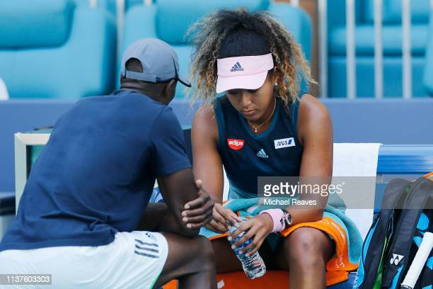 Naomi Osaka of Japan talks to her coach Jermaine Jenkins during a changeover against Yanina Wickmayer of Belgium during Day 5 of the Miami Open...