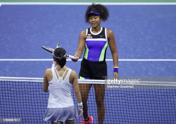 Naomi Osaka of Japan taps rackets after winning during her Women's Singles first round match against Misaki Doi of Japan on Day One of the 2020 US...
