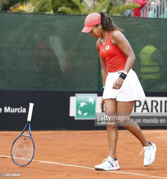Naomi Osaka of Japan throws her racket after losing a game during her singles match against Sara Sorribes Tormo of Spain in the Fed Cup Qualifiers in...