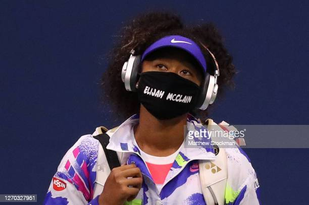 Naomi Osaka of Japan walks in wearing a mask with the name Elijah McClain on it before her Women's Singles second round match against Camila Giorgi...