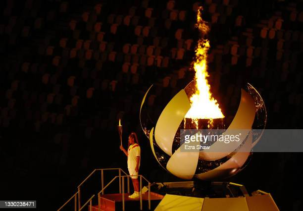 Naomi Osaka of Team Japan carries the Olympic torch towards the Olympic cauldron during the Opening Ceremony of the Tokyo 2020 Olympic Games at...