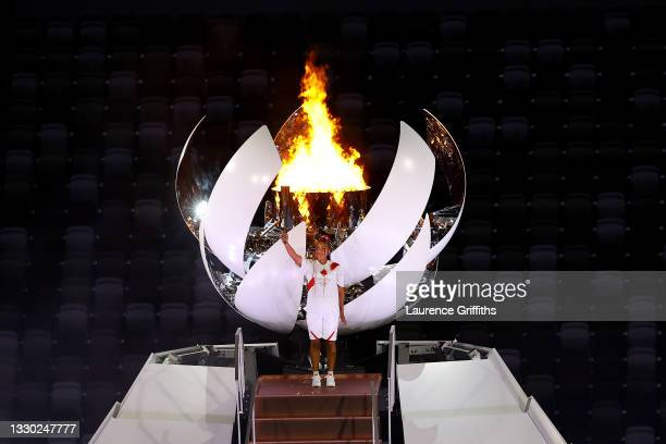 Naomi Osaka of Team Japan holds up the Olympic torch after lighting the Olympic cauldron during the Opening Ceremony of the Tokyo 2020 Olympic Games...
