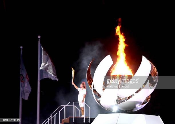 Naomi Osaka of Team Japan lights the Olympic cauldron with the Olympic torch during the Opening Ceremony of the Tokyo 2020 Olympic Games at Olympic...