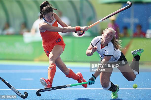 Naomi van As of the Netherlands shoots at goal under pressure from Nike Lorenz of Germany who was hit on the head with her stick during the womens...