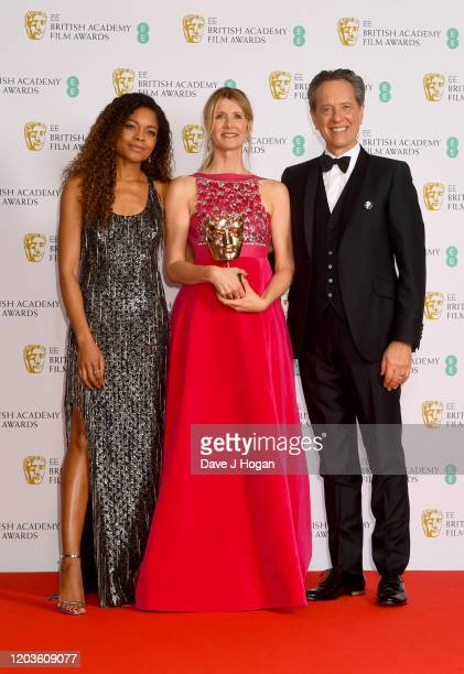 Naomie Harris and Richard E. Grant present Laura Dern with the Bafta for Best Supporting Actress in the Winners Room during the EE British Academy...