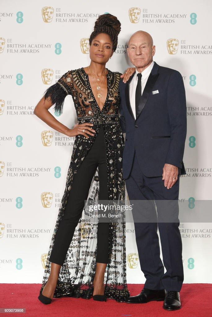 Naomie Harris (L) and Sir Patrick Stewart pose in the press room during the EE British Academy Film Awards (BAFTA) held at Royal Albert Hall on February 18, 2018 in London, England.