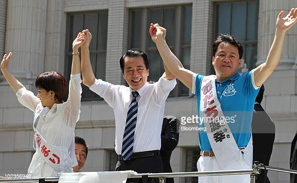 Naoto Kan Japan's prime minister and president of the Democratic Party of Japan center raises the arms of his party candidates Mari Okabe left and...