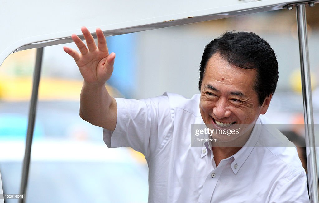Naoto Kan, Japan's prime minister and president of the Democratic Party of Japan (DPJ), waves as he arrives for a campaign rally for the July 11 Upper House election in Yokohama, Japan, on Sunday, July 4, 2010. Kan said he'll call a lower house election before doubling the nation's sales tax to 10 percent to bolster finances. Photographer: Tomohiro Ohsumi/Bloomberg via Getty Images