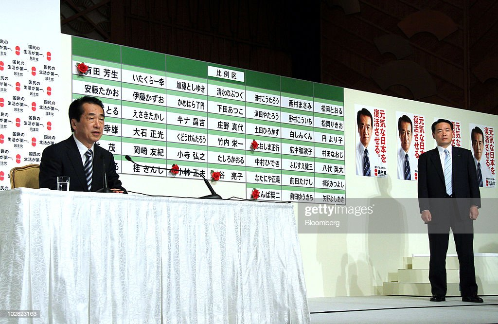 Naoto Kan, Japan's prime minister and president of the Democratic Party of Japan (DPJ), left, speaks as a security officer stands during a news conference at the party's election center in Tokyo, Japan, on Monday, July 12, 2010. Kan lost control of parliament's upper house, undermining legislative efforts to cut the world's largest public debt and creating the possibility of a third leadership change in a year. Photographer: Haruyoshi Yamaguchi/Bloomberg via Getty Images