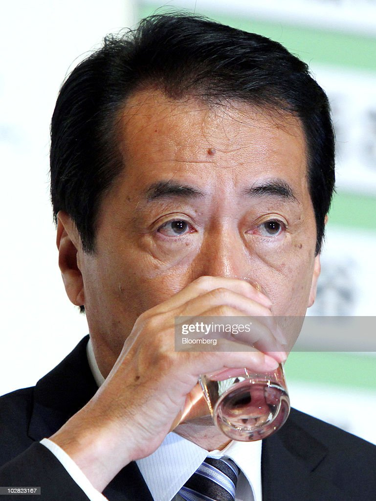 Naoto Kan, Japan's prime minister and president of the Democratic Party of Japan (DPJ), drinks a glass of water during a news conference at the party's election center in Tokyo, Japan, on Monday, July 12, 2010. Kan lost control of parliament's upper house, undermining legislative efforts to cut the world's largest public debt and creating the possibility of a third leadership change in a year. Photographer: Haruyoshi Yamaguchi/Bloomberg via Getty Images