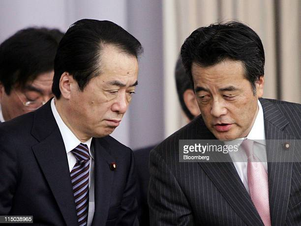 Naoto Kan Japan's prime minister left speaks with Katsuya Okada secretary general of the Democratic Party of Japan during a meeting with lawmakers of...