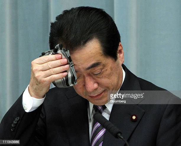 Naoto Kan Japan's prime minister uses a handkerchief during a news conference at his official residence in Tokyo Japan on Friday April 1 2011 The...