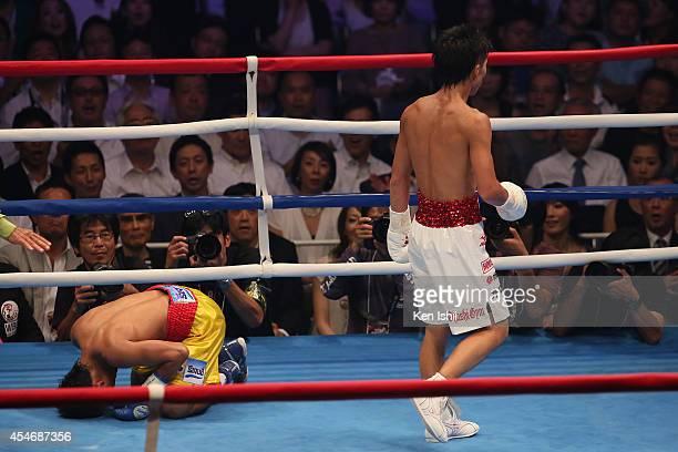 Naoya Inoue of Japan walks as Samartlek Kokietgym of Thailand falls during the WBC light flyweight title bout between Naoya Inoue of Japan and...