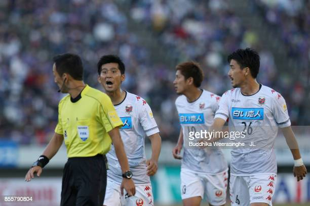Naoya Kikuchi and Consadole Sapporo players protest to referee Jumpei Iida after the penalty decision during the J.League J1 match between Sanfrecce...