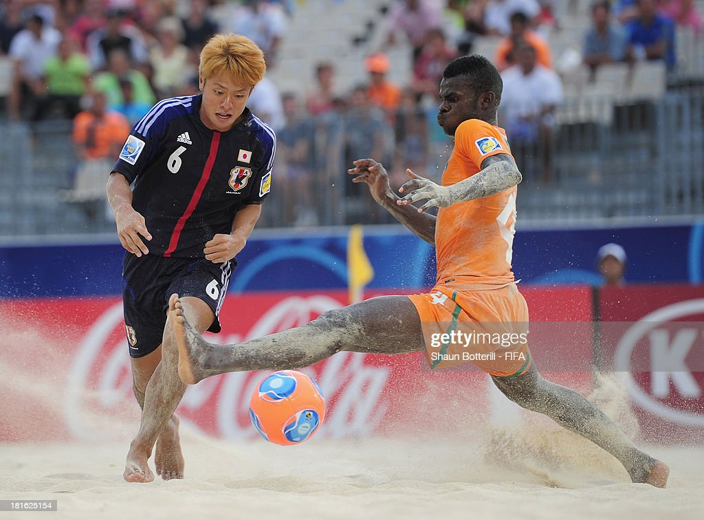 Naoya Matsuo of Japan is tackled by Guy Djedjed of Ivory Coast during the FIFA Beach Soccer World Cup Tahiti 2013 Group D match between Japan and Ivory Coast at the Tahua To'ata stadium on September 22, 2013 in Papeete, French Polynesia.