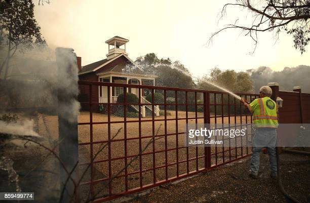 Napa Valley public worker sprays water on a building as an out of control wildfire moves through the area on October 9 2017 in Yountville California...