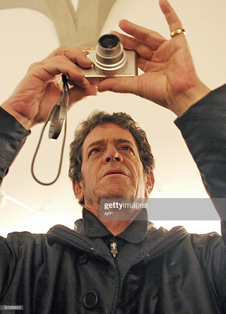 International pop star Lou Reed takes a picture of a placard promoting his own photo exhibit at P.A.N. (Arts Palace of Naples) 09 March 2006 in Naples. Reed inaugurated the exibhition called 'Lou Reed New York', a work around the theme of New York's light, for the first time in Europe. AFP PHOTO / Mario LAPORTA