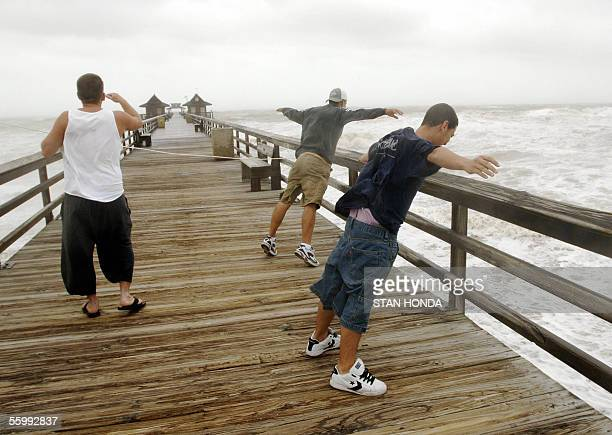 John Morelo and Lorenzo Exposito lean into the strong winds while Jon Walker scans the horizon 24 October on the Naples Pier as the trailing edge of...