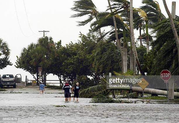 People walk down a flooded street in Naples Florida 24 October after the trailing edge of Hurricane Wilma passed through Wilma was downgraded Monday...