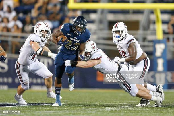 Napoleon Maxwell of the Florida International Panthers runs with the ball past the attempted tackle by Cole McCubrey of the UMass Minutemen at FIU...