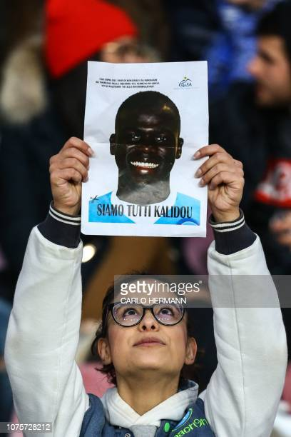 A Napoli fan holds a portrait of Napoli's Senegalese defender Kalidou Koulibaly reading We are all Kalidou prior to the Italian Serie A football...