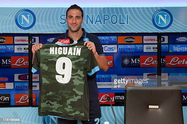 Napoli new forward Argentinian Gonzalo Higuain, former Real Madrid player, poses with an official football team jersey during his first press...