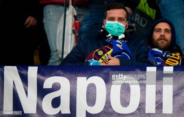 A Napoli supporter wearing a protective face mask attends the UEFA Champions League round of 16 firstleg football match between SSC Napoli and FC...