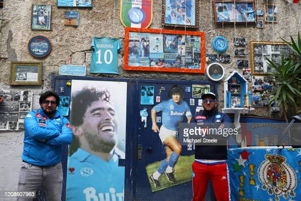Napoli supporters pose amongst street art showing ex Napoli player Diego Maradona in the city of Naples ahead of the UEFA Champions League round of...