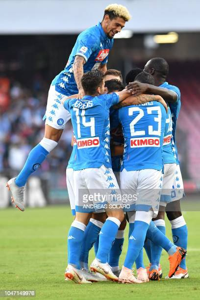 Napoli's Algerian forward Adam Ounas celebrates with his team mates after scoring during the Italian Serie A football match Napoli vs Sassuolo at the...
