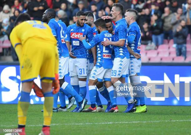 Napoli's Algerian forward Adam Ounas celebrates with teammates after scoring a goal during the Italian Serie A football match between Napoli and...