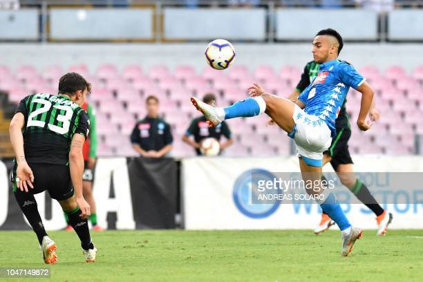 Napoli's Algerian forward Adam Ounas shoots and scores during the Italian Serie A football match Napoli vs Sassuolo at the San Paolo Comunal Stadium...