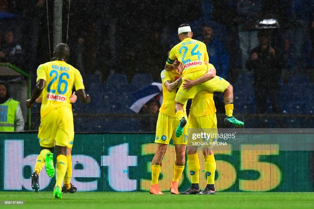 Napoli's forward from Poland Arkadiusz Milik (hidden) celebrates with teammates after scoring during the Italian Serie A football match Sampdoria vs Napoli on May 13, 2018 at the Luigi Ferraris stadium in Genova. (Photo by Miguel MEDINA / AFP) / The erroneous mention[s] appearing in the metadata of this photo by Miguel MEDINA has been modified in AFP systems in the following manner: [May 13] instead of [April 13]. Please immediately remove the erroneous mention[s] from all your online services and delete it (them) from your servers. If you have been authorized by AFP to distribute it (them) to third parties, please ensure that the same actions are carried out by them. Failure to promptly comply with these instructions will entail liability on your part for any continued or post notification usage. Therefore we thank you very much for all your attention and prompt action. We are sorry for the inconvenience this notification may cause and remain at your disposal for any further information you may require.