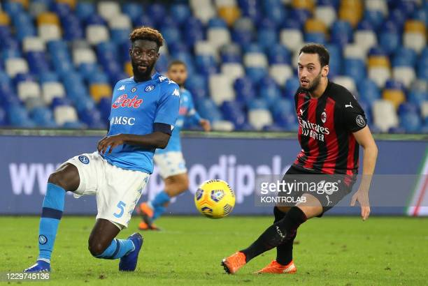 Napoli's French midfielder Tiemoue Bakayoko fights for the ball with AC Milan's Turkish midfielder Hakan Calhanoglu during the Serie A football match...