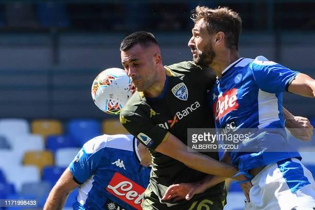 Napoli's Greek defender Konstantinos Manolas scores a header during the Italian Serie A football match Napoli vs Brescia on September 29 2019 at the...