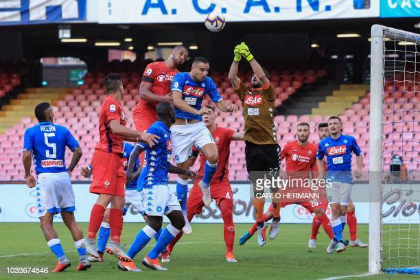 Napoli's Greek goalkeeper Orestis Karnezis deflects a shot under pressure from Fiorentina's Brazilian defender Vitor Hugo during the Italian Serie A...
