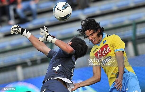 Napoli's Huruguayan forward Edinson Roberto Cavani jumps for the ball against Cagliari's goalkeper Michael Agazzi during their Italian Serie A...